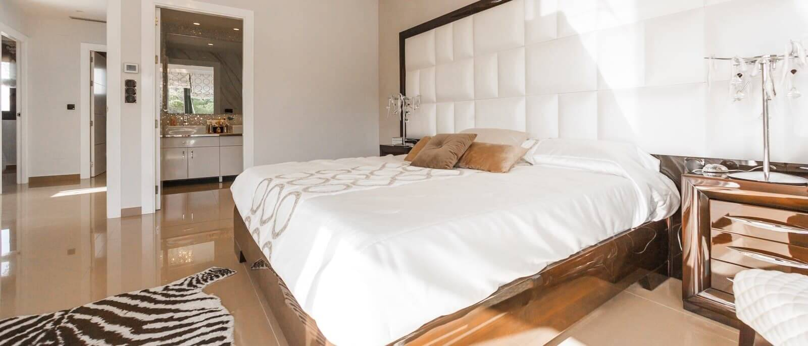 a look into a modern bedroom with white headboard and bronze furnishing