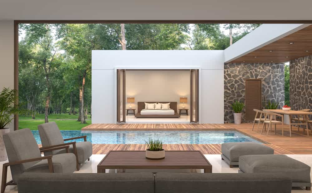 A coastal design of a poolside bedroom with an accent wall and timber decking